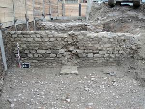 Mur de soutènement antique bordant une voie orientée nord-sud.