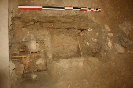Inhumation primaire avec crâne en réduction et traces de cercueils.